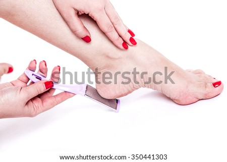 woman treats dehydrated skin heels legs pedicure tool grater for heels - stock photo