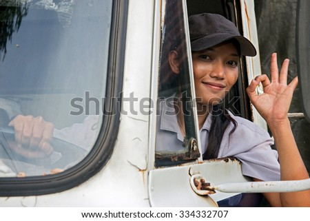 woman truck driver in the car. young Asian woman driving a truck. Truck driver shows from open window the perfect gesture. Successful gesture O.K. from driver of truck. Asian lorry driver. - stock photo