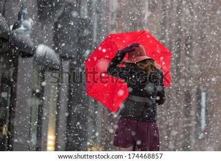 Woman try hold hat and umbrella from behind - stock photo