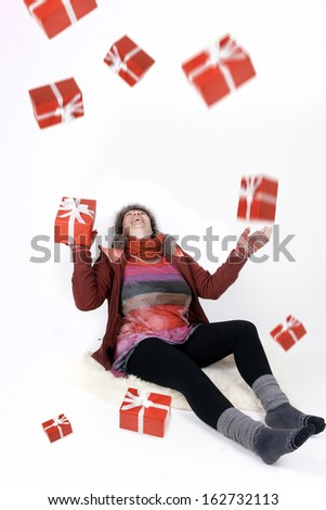 Woman trying to catch christmas presents falling form heaven - stock photo