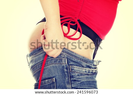 Woman trying to get in to old jeans. - stock photo