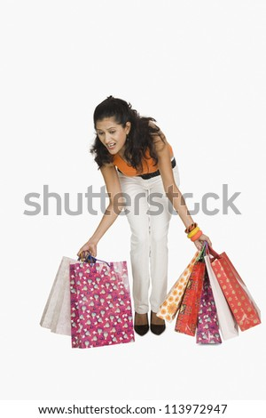 Woman trying to lift shopping bags - stock photo