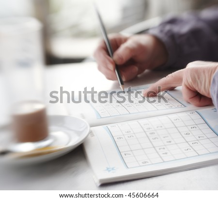 Woman trying to solve Sudoku Puzzle - window, sunlight, and coffee - stock photo