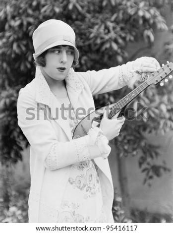 Woman tuning mandolin outside - stock photo