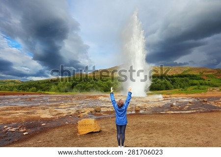 Woman -turist delighted geyser Strokkur. High column of hot water and steam . Gushing geyser Strokkur.  - stock photo