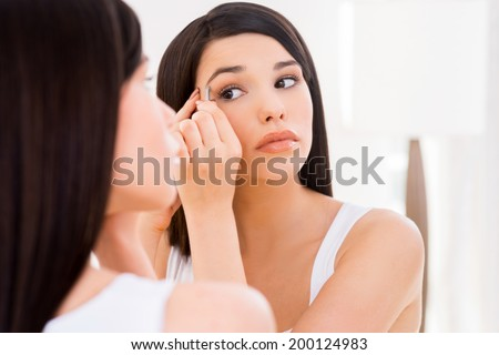 Woman tweezing eyebrows. Beautiful young woman tweezing eyebrows while looking at the mirror - stock photo