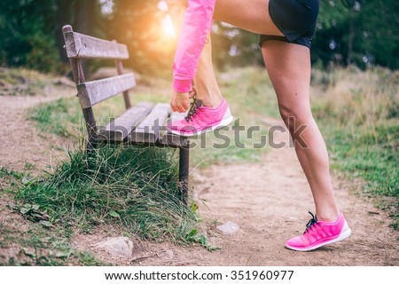 Woman tying shoelaces before start running - Sportive girl jogging in a park , close up on running shoes - Concepts about sport and lifestyle - stock photo