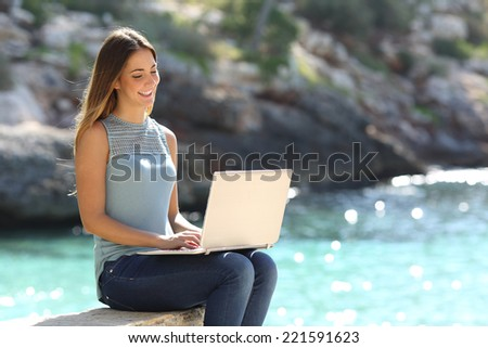 Woman typing on a laptop in a tropical beach with a turquoise sea in the background - stock photo