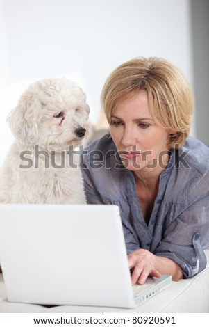 Woman typing on laptop computer next to small white dog - stock photo