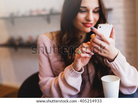 Woman typing write  message on smart phone in a  modern cafe. Cropped image of young  pretty girl sitting at a table with  coffee or cappuccino  using mobile phone. - stock photo