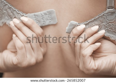 Woman undressing brassiere. Close-up rear view photo - stock photo