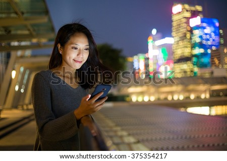 Woman use cellphone at night - stock photo