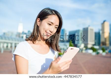Woman use of mobile phone at Hong Kong city - stock photo
