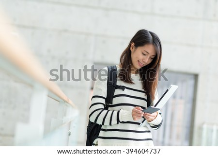 Woman use of mobile phone in university - stock photo