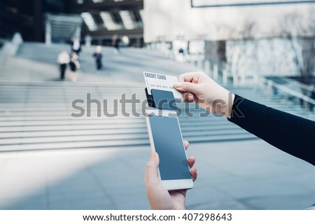 Woman use of mobile phone to pay. Swiping Credit/Debit Card With Card Reader outdoors in the city - stock photo