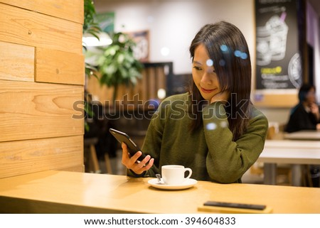 Woman use of smart phone in coffee shop - stock photo