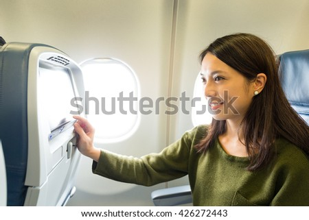 Woman use of the entertainment unit on airplane - stock photo