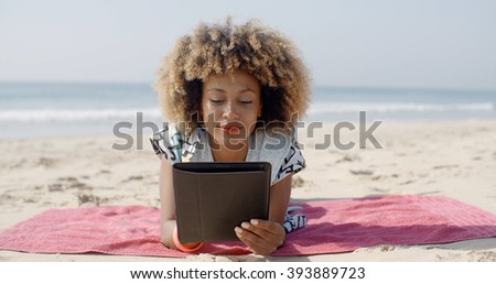 Woman Uses A Tablet On The Beach - stock photo