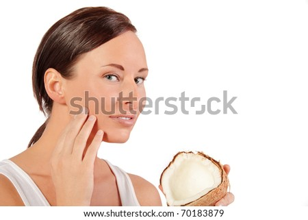 Woman uses coconut cream for her face - stock photo