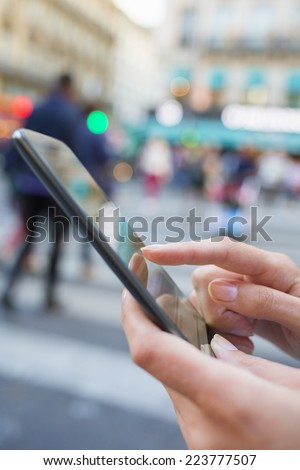 Woman uses her mobile phone on the street in Paris - stock photo
