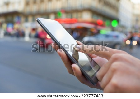 Woman uses her smart phone on the street in Paris - stock photo