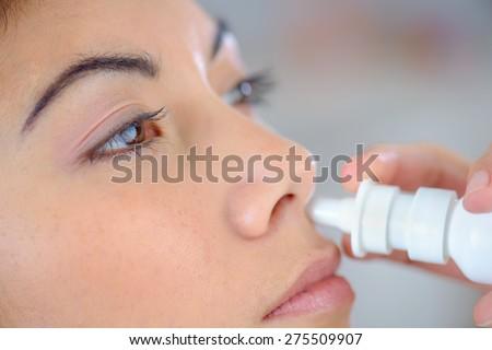 Woman using a nasal spray - stock photo
