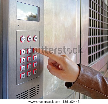 Woman using a security keypad - stock photo