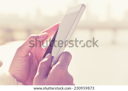 woman using a smart phone with sunrise background - stock photo