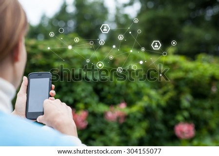 Woman using a smartphone in the garden - stock photo