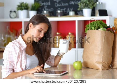 Woman using a tablet computer while drinking tea in her kitchen . - stock photo