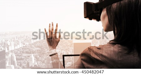 Woman using a virtual reality device against new york - stock photo