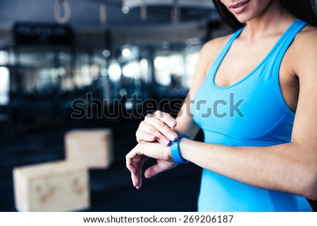 Woman using activity tracker at gym - stock photo