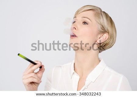 Woman using alternative cigar over grey - stock photo