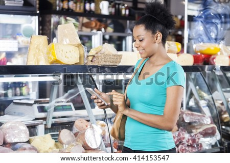 Woman Using Cell Phone In Grocery Shop - stock photo