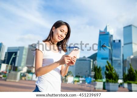 Woman using cellphone at city of Hong Kong - stock photo
