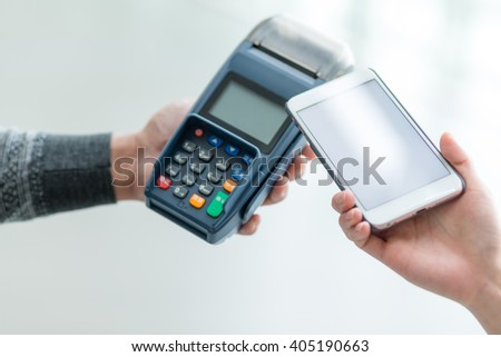 Woman using cellphone to pay with mobile phone - stock photo