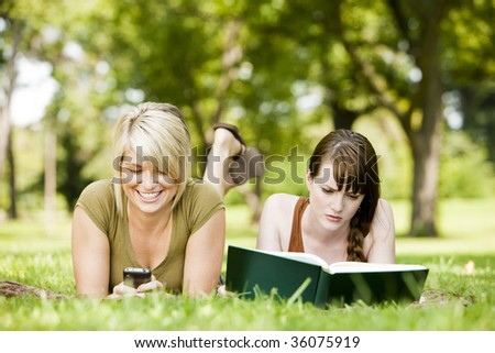 Woman using cellphone while her friend reads a book - stock photo