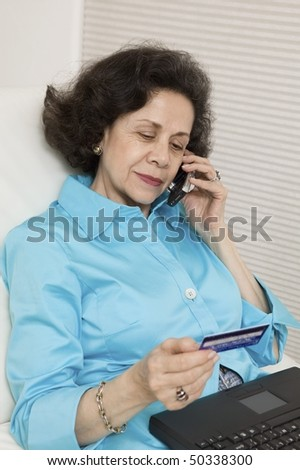 Woman Using Credit Card and Cell Phone to Make Online Purchase - stock photo
