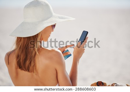 Woman using credit card on vacation shopping online with mobile phone at the beach - stock photo