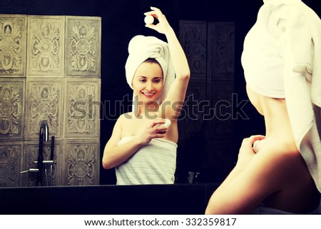 Woman using deodorant in the bathroom. - stock photo