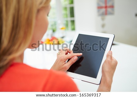 Woman Using Digital Tablet At Home In Kitchen - stock photo