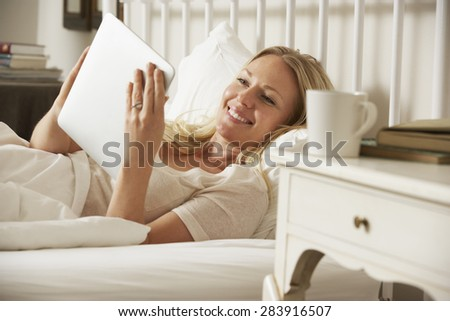 Woman Using Digital Tablet In Bed At Home - stock photo