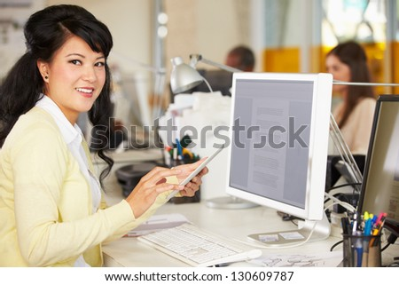 Woman Using Digital Tablet In Busy Creative Office - stock photo