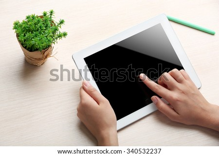 Woman using digital tablet on workplace close up - stock photo