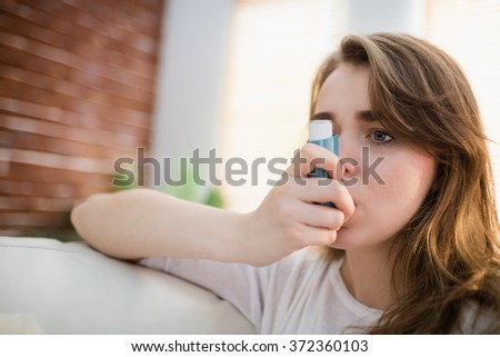 Woman using her inhaler on couch in the living room - stock photo