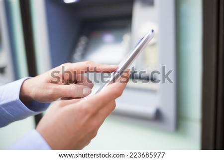 Woman using her mobile phone in front of a cash machine - stock photo