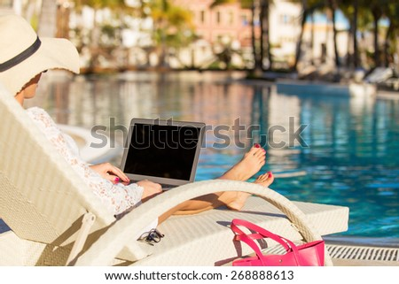 Woman using laptop computer by the swimming pool - stock photo