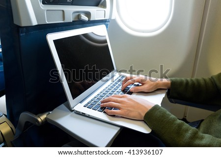 Woman using laptop computer on airplane - stock photo