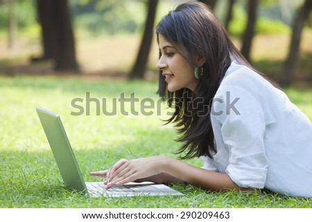 Woman using laptop on campus - stock photo