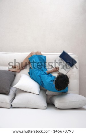 Woman using laptop on couch in living room - stock photo